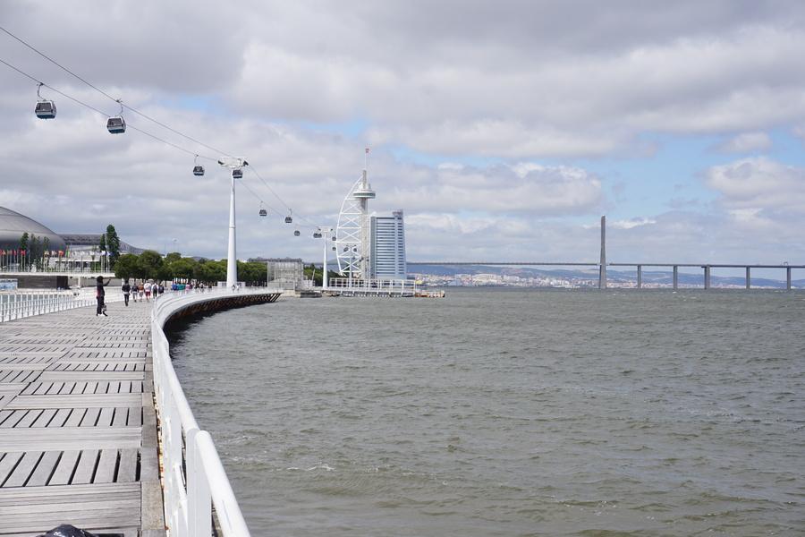 La promenade en bord de Tage avec la tour et le pont Vasco de Gama au fond